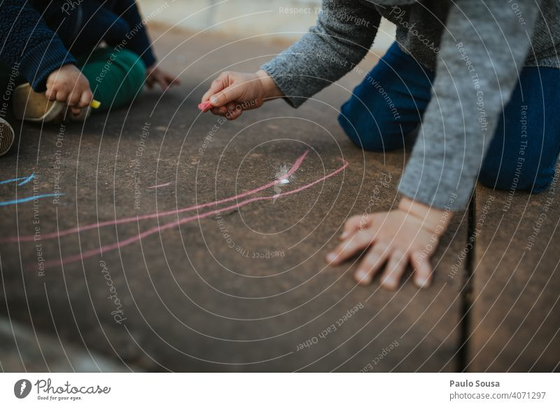 Child drawing with colored chalk on the floor Chalk Chalk drawing Creativity Drawing Infancy Street Playing Joy Children's game Art Leisure and hobbies