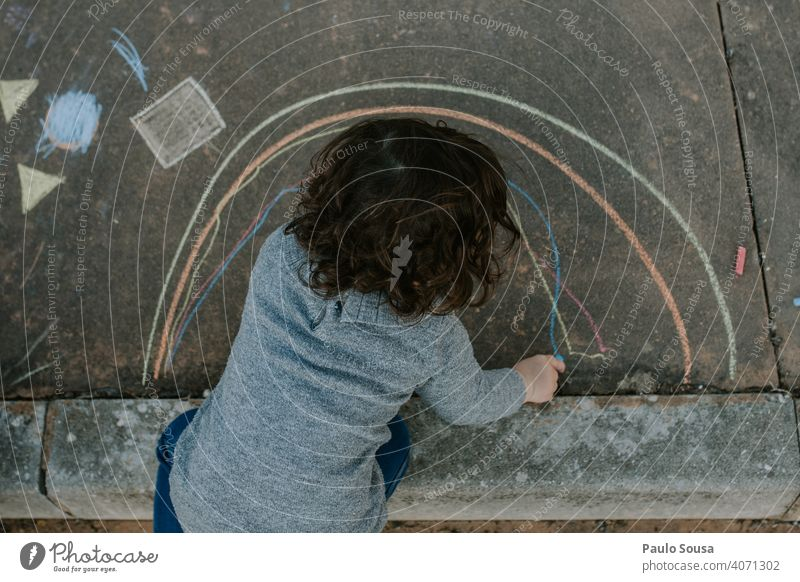 Child drawing with colored chalk on the floor Chalk Chalk drawing childhood Painting and drawing (object) Street Playing Drawing Infancy Asphalt Street painting