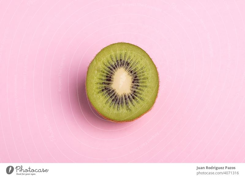 Close-up of a kiwi sliced on pastel pink background. fruit minimal isolated nobody concept healthy cut vegetarian sweet food summer juice color flat green