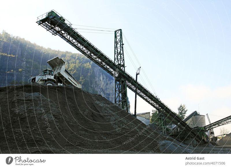 Eine Kiesgrube mit Arbeitsgeräten und LKW im Gebirge kiesgrube kieswerk lkw industrie förderband arbeit arbeitsgeräte sand bauindustrie firma gebirge baugewerbe