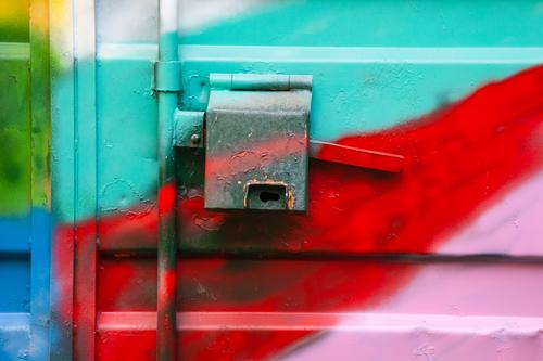 Metal container colorfully sprayed with graffiti Container Door handle Closure Graffiti variegated neon Neon Flashy locked Industry Closed Structures and shapes