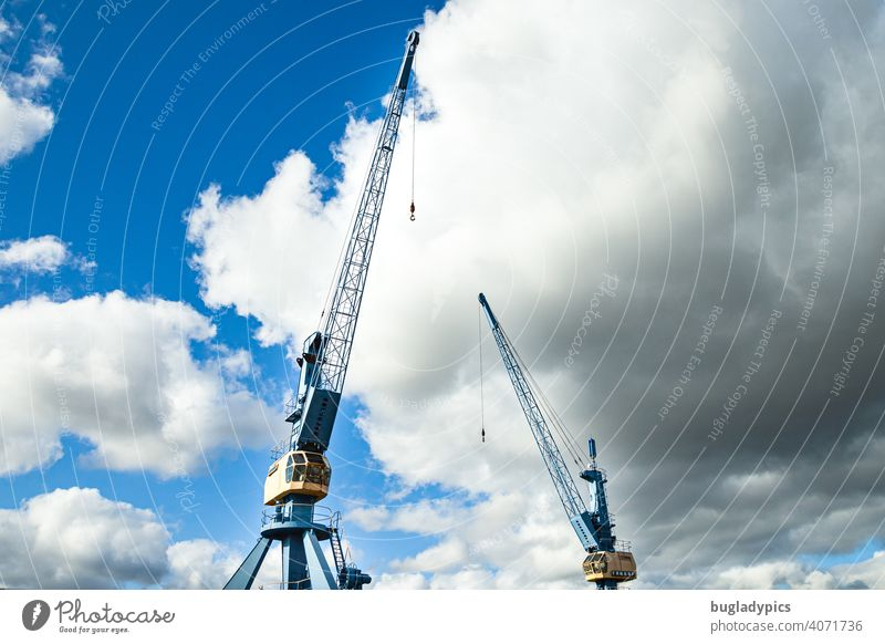 Two blue and yellow cranes in front of cloudy sky in a harbour Crane loading crane Blue sky Clouds Clouds in the sky Yellow Harbour Construction site