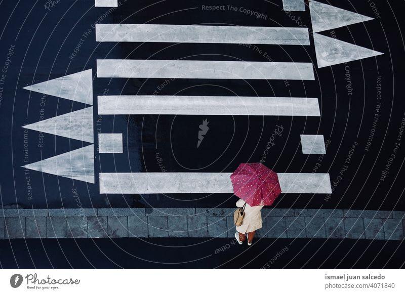 woman with an umbrella on the crosswalk people person rain rainy raining day rainy day water human pedestrian street city urban bilbao spain walking lifestyle