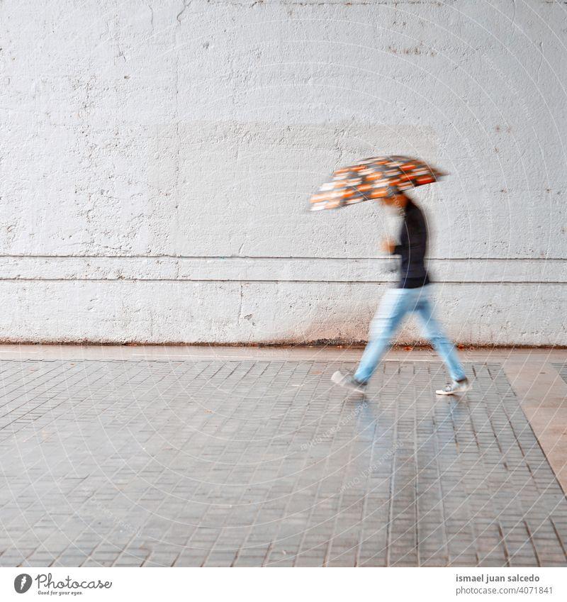defocused man with an umbrella in rainy days in spring season people person raining water human pedestrian street city urban bilbao spain walking lifestyle
