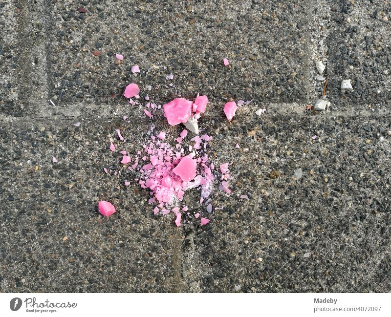 Dropped crumbled pink candy on grey pavement in Oerlinghausen near Bielefeld in the Teutoburg Forest in East Westphalia-Lippe Candy Lozenge Pink Broken Crumbs