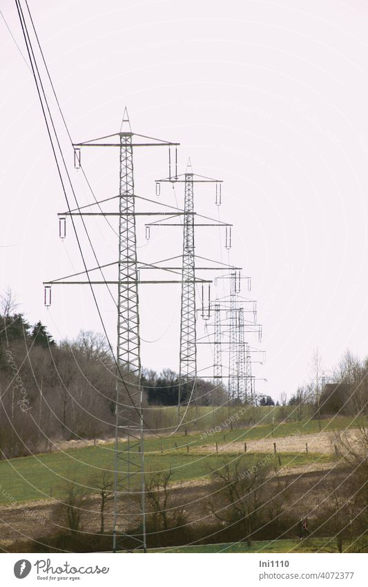 a row of metal power poles in the landscape in cloudy weather Fir pole Electricity pylon co2 high voltage Power lines energy Technology Cable Metal