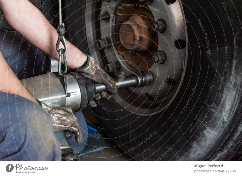 Tire workshop operator who uses a machine to mount or remove a truck wheel. tire mechanic tool repair fix service maintenance vehicle tyre equipment industrial