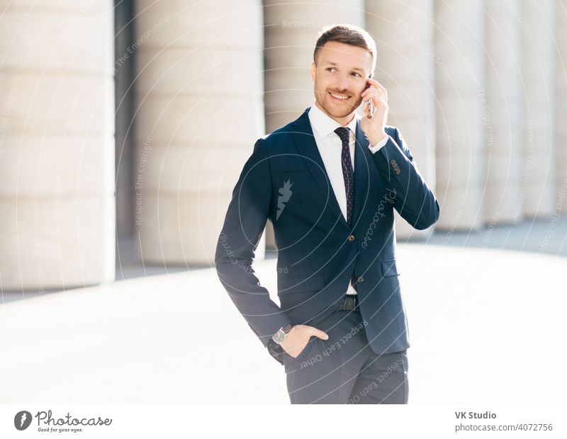 Portrait of successful male manager satisfied with mobile tariffs, makes phone call, uses banking service operator, wears formal suit, stands in urban setting outsie. Professional man worker