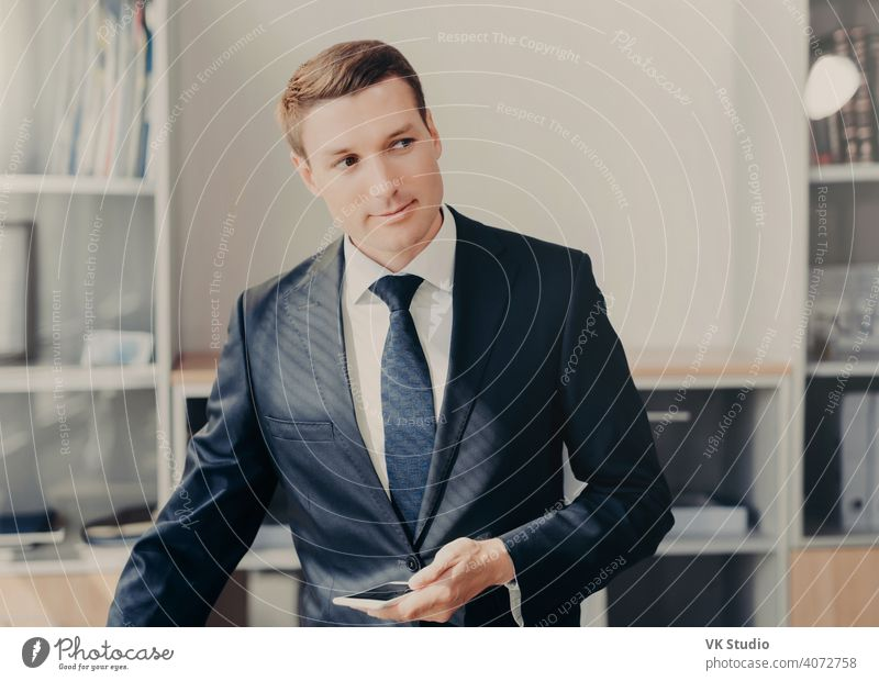Horizontal shot of handsome male manager in stylish clothes, uses smart phone for checking information about entrepreneurship, reads news in web page, connected to wireless internet, stands at office