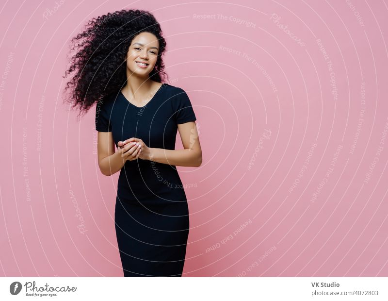 Photo of happy cheerful dark skinned curly woman dresses for casual event, smiles positively, enjoys pleasant talk with man, keeps hands together, stands indoor, free space aside for your text