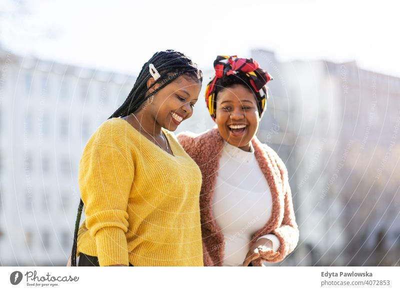 Beautiful happy girlfriends talking and smiling in city diversity diverse people love outdoors day positivity confident carefree woman young adult casual