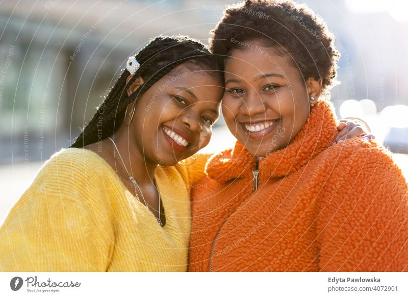 Portrait of two beautiful women standing together outdoors diversity diverse people love day positivity confident carefree woman young adult casual attractive