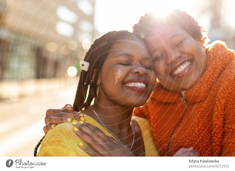 Portrait of two beautiful happy girlfriends embracing outdoors diversity diverse people love day positivity confident carefree woman young adult casual