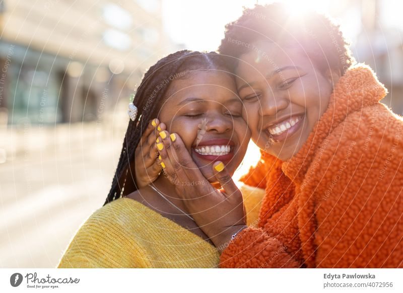 Two beautiful Afro american women having fun together in the city diversity diverse people love outdoors day positivity confident carefree woman young adult
