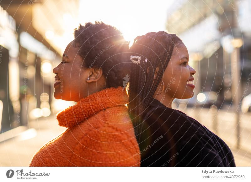 Two beautiful Afro american women standing back to back in city diversity diverse people love outdoors day positivity confident carefree woman young adult