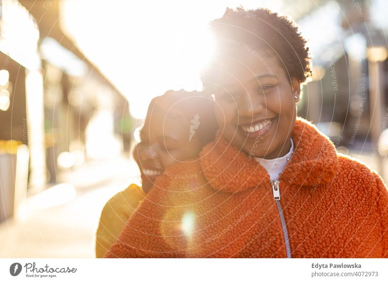 Two beautiful Afro american women in an urban city area diversity diverse people love outdoors day positivity confident carefree woman young adult casual