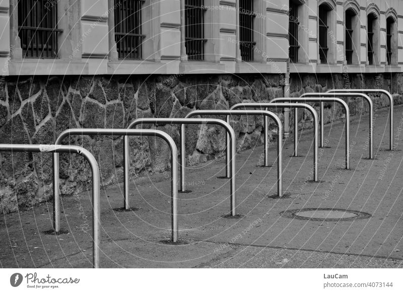 Empty metal bike racks outside a school in the Corona pandemic Bicycle Cycling Bicycle rack Wheel Symmetry symmetric wheel stand Abstract Mobility Vacancy