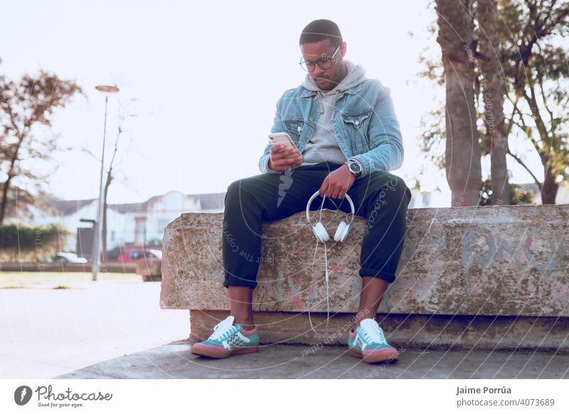 black boy sitting on a bench listening to music male earphones outdoors alone young 1 adult man smiling people technology path cheerful happiness closeup fun
