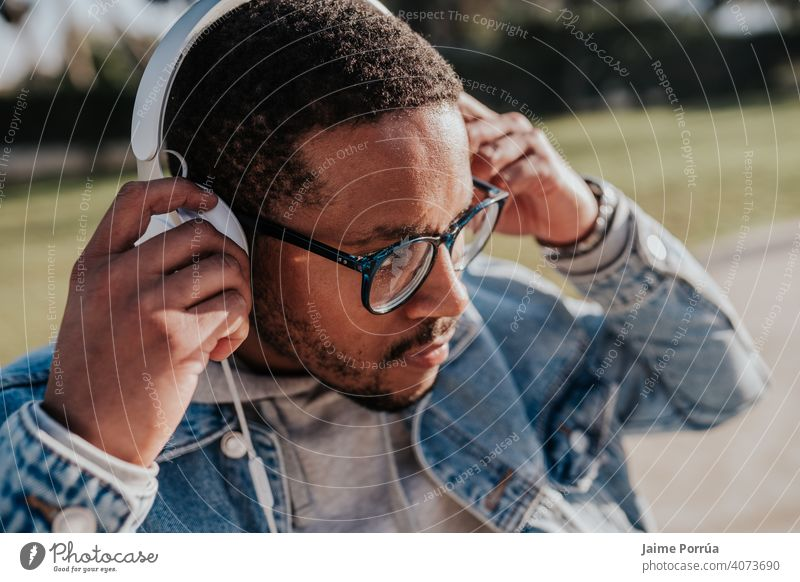 black boy in park listening to music with headphones afro holding youth trendy teenage casual attire skate young portrait sunset lifestyle street skater 1 male