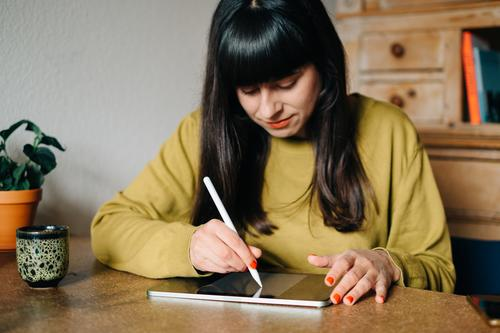 A woman sits at the table and draws or writes something on a tablet Painting (action, artwork) Write Draw pen Ipad Apple Pen Creativity Digital Graphic Designer