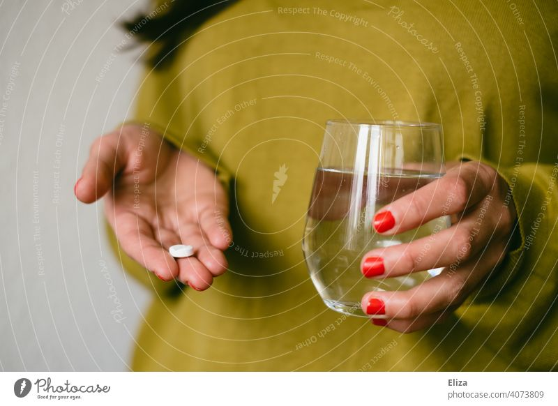 A woman holds a tablet and a glass of water in her hands. Taking medicine. Pill Medication headache tablet Ibuprofen Water Tumbler Healthy Illness Painkiller