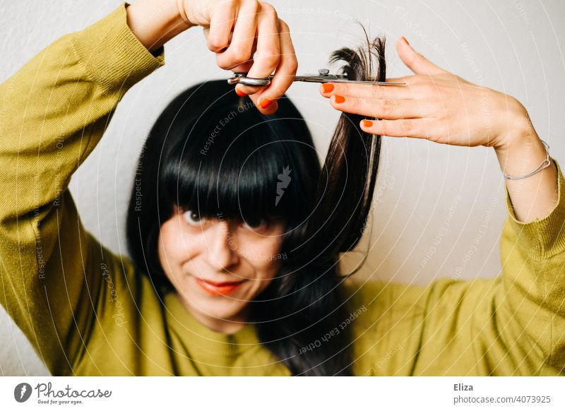 A brown haired woman cuts her own hair Haircut Hair Stylist do it oneself yourself at home Dark-haired recut lockdown DIY Hairdresser Woman Hair and hairstyles