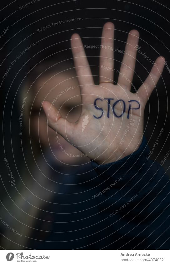 Stop! Woman holds your hand, which says Stop, against a window. stop Hold Border Hand Palm of the hand Human being Cancelation set boundaries say no Quit