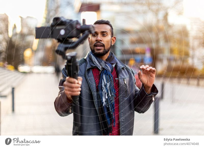 Man filming a vlog with camera in the city video blogger vlogger journalist influencer photographer technology travel tourist explorer freelancer reportage