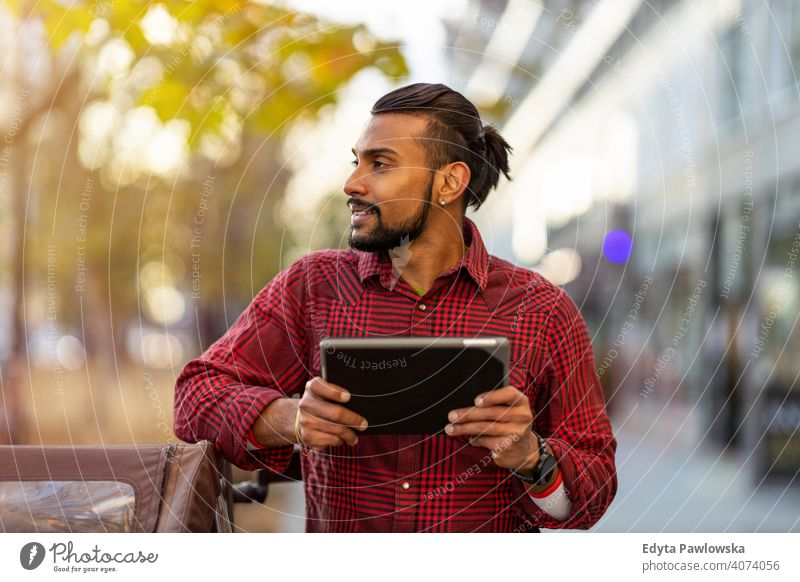 Young man using digital tablet outdoors at urban setting Sinhalese asian Indian bearded outside street standing city Warsaw one casual lifestyle guy attractive