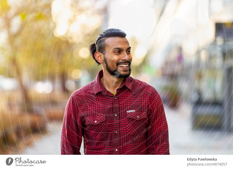 Portrait of a handsome young man on the city street Sinhalese asian Indian bearded outside urban standing outdoors Warsaw one casual lifestyle guy attractive