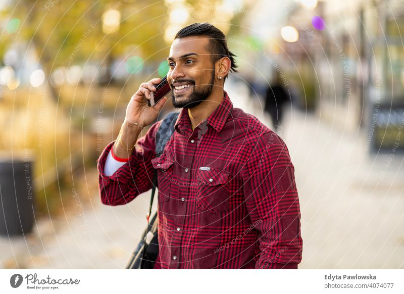 Handsome young man using mobile phone at the street Sinhalese asian Indian bearded outside urban standing outdoors city Warsaw casual lifestyle guy attractive