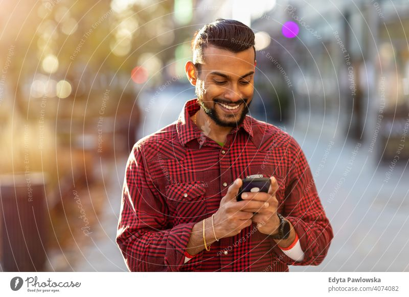 Young man walking on the street and text messaging Sinhalese asian Indian bearded outside urban standing outdoors city Warsaw one casual lifestyle guy