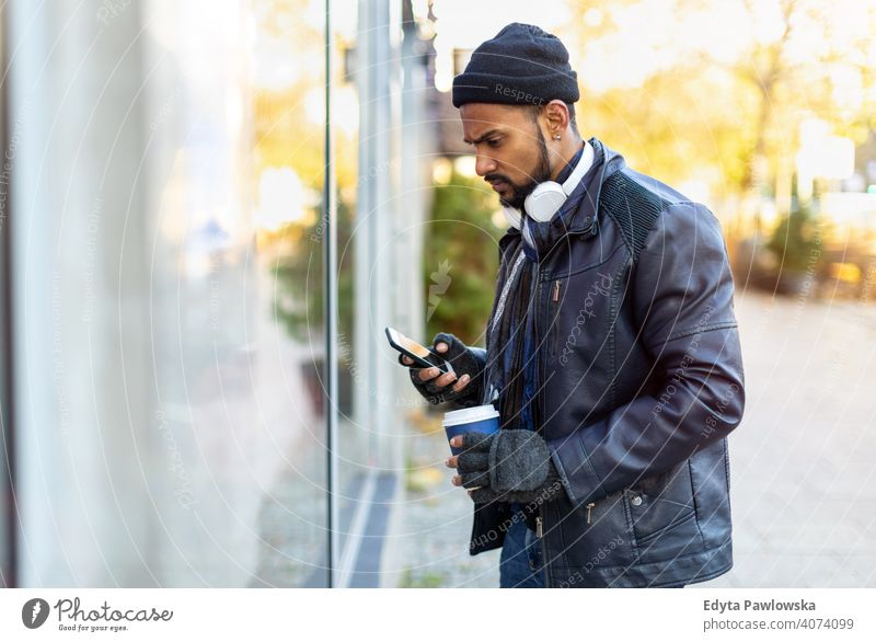 Young man window shopping on city street Sinhalese asian Indian bearded outside urban standing outdoors Warsaw one casual lifestyle guy attractive handsome