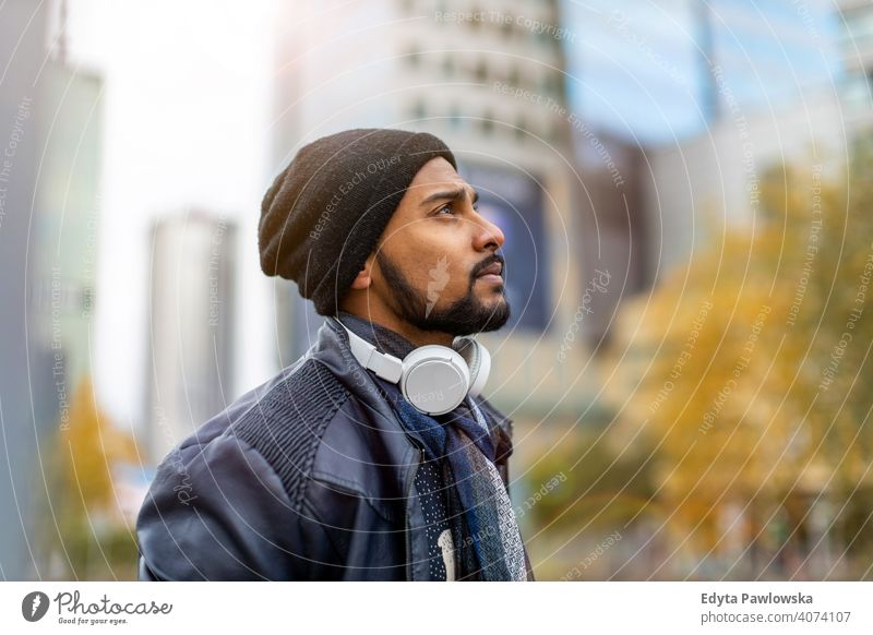 Portrait of a stylish young man standing in a city street Sinhalese asian Indian bearded outside urban outdoors Warsaw one casual lifestyle guy attractive
