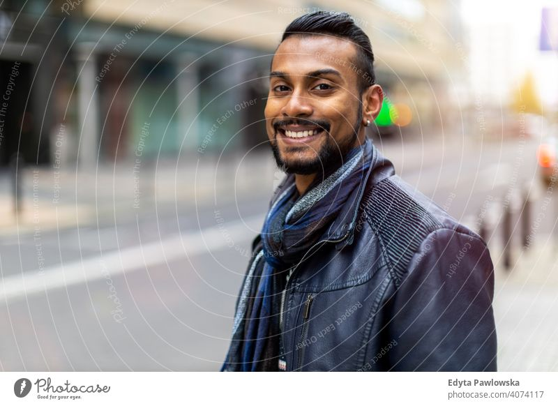Portrait of a beautiful smiling man Indian ethnicity looking at the camera Sinhalese asian bearded outside street urban standing outdoors Warsaw one casual