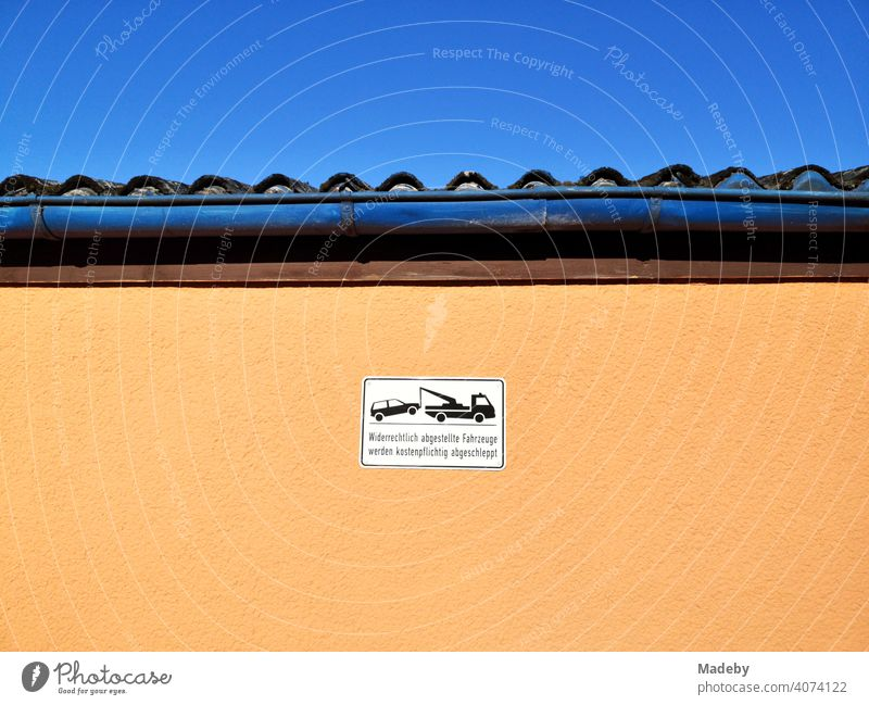 Sign for illegal parking on a facade in apricot under blue sky and sunshine in summer in Oerlinghausen near Bielefeld on the Hermannsweg in the Teutoburg Forest in East Westphalia-Lippe