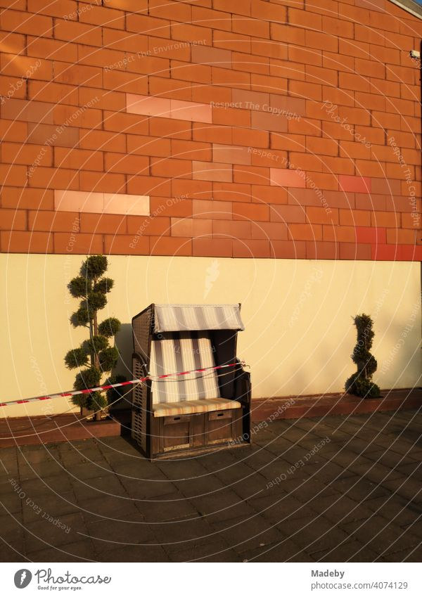 Beach chair with barrier tape because of Corona with whimsically formed plants in front of house wall in nature colors in the light of the setting sun in Oerlinghausen near Bielefeld at the Hermannsweg in the Teutoburg Forest in East Westphalia-Lippe