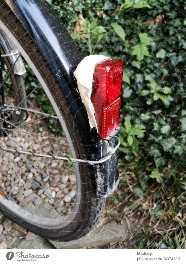 Red rear light fixed with adhesive tape to a black mudguard on a bicycle in front of a green hedge in Oerlinghausen near Bielefeld on the Hermannsweg in the Teutoburg Forest in East Westphalia-Lippe