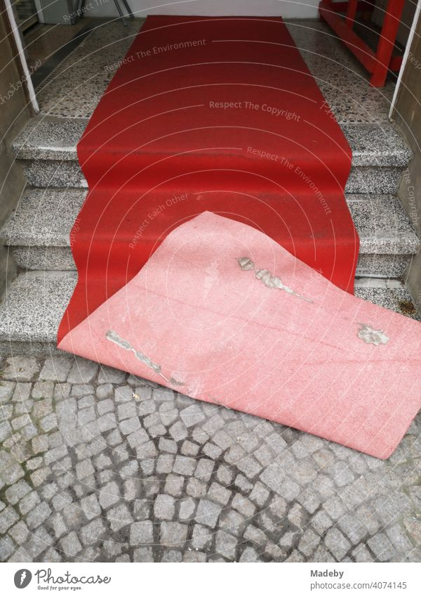 Red blown carpet on old grey steps and grey cobblestone pavement at the entrance of a hairdresser in the old town of Oerlinghausen near Bielefeld at the Hermannsweg in the Teutoburg Forest in East Westphalia-Lippe