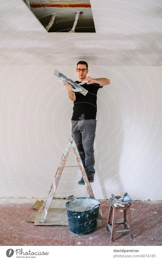 Builder working picking plaster with spatula mason builder plasterer picking up gypsum plaster trowel climbed on ladder home improvement reform house stepladder