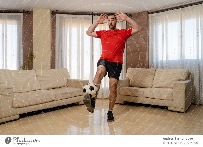 Bearded man in fit shape dressed in black and red sportswear controlling a soccer ball with his foot admirer adult home supporter person portrait fan emotion