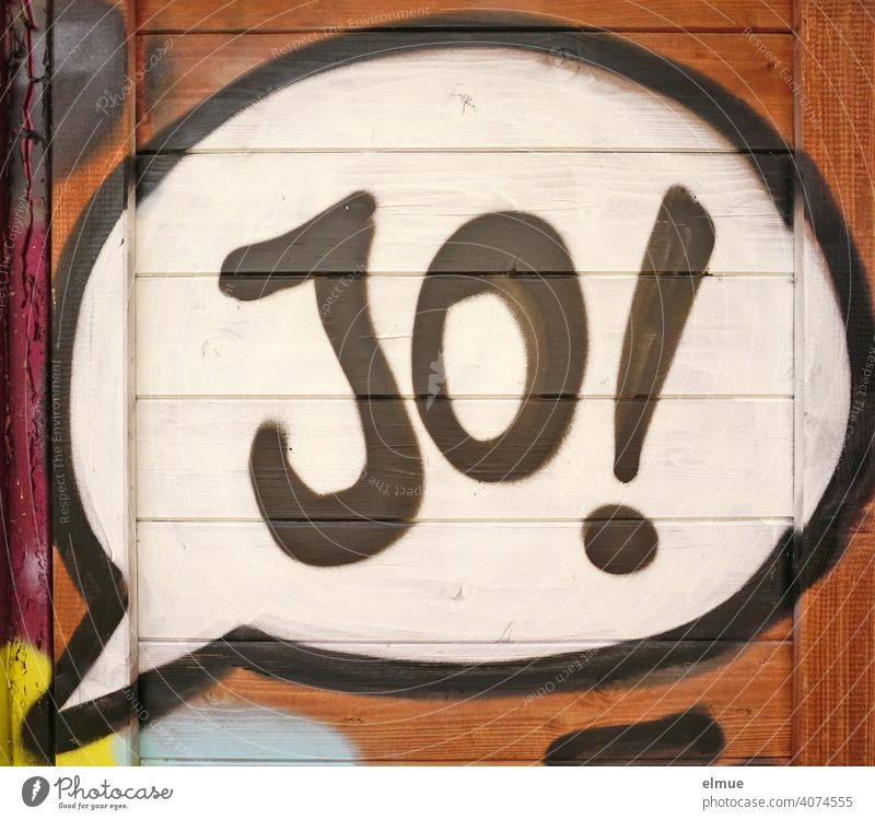 """In the speech bubble of his graffito on the wooden wall the sprayer has written """" Jo ! """" written / think positive yo Yes Graffito Graffiti youth language"""