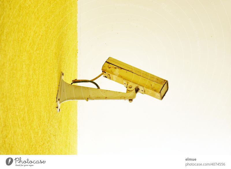 old, broken, yellow painted surveillance camera on a yellow wall / control / observation Surveillance camera Video surveillance Testing & Control Yellow