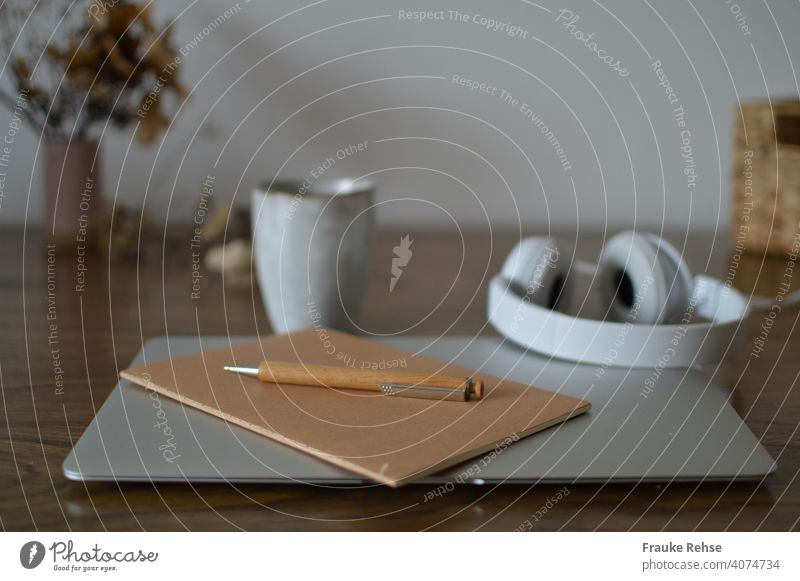 Desk with laptop, notebook, pen in foreground - headphones and mug, tray and flowers in background Home Office Notebook Workplace home office at home thoughts