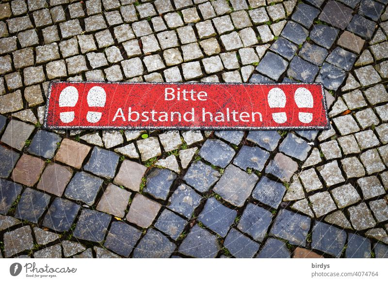 Please keep your distance. Marking on cobblestones of a weekly market keep sb./sth. apart gap Hygiene rules corona Protection Risk of infection prevention