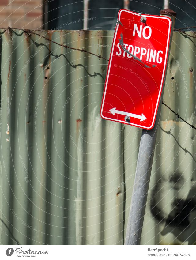 No stopping sign in front of corrugated iron Road sign Signs and labeling Characters Road traffic Deserted Colour photo English Arrow Barbed wire