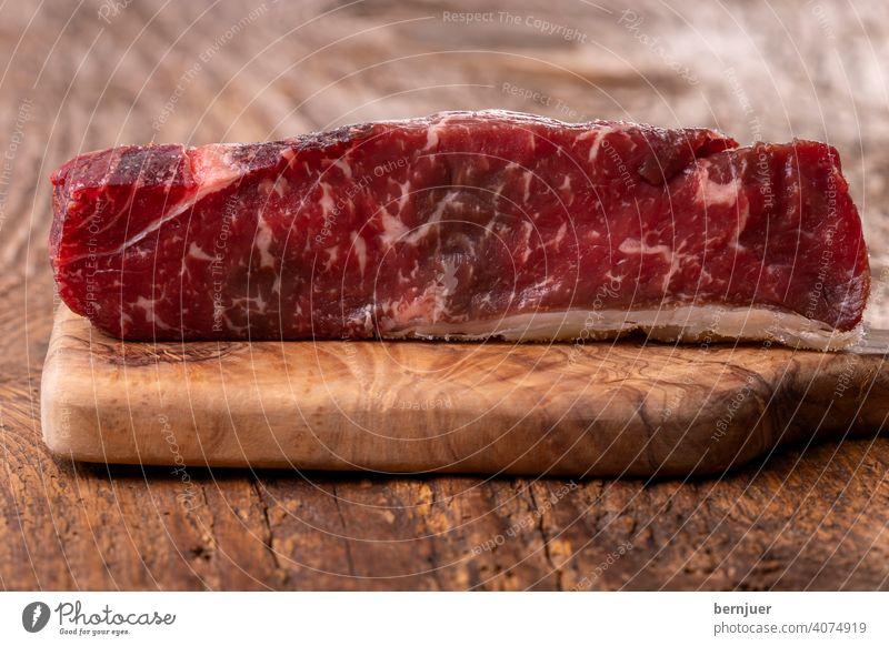 Rohes Steak auf Olivenholz Rindlende Sirloin Textur einzeln Medaillon Fett dryage mignon Filet Board roh dryage steak seitenansicht Fleisch Angus Essen Prime