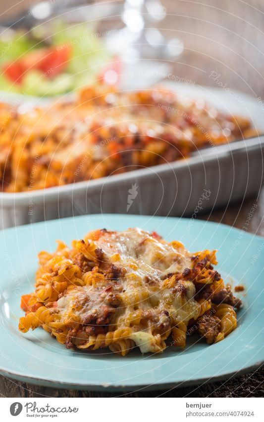 pasta au gratin with salad on wood rigatoni baked Cheese Wood Rustic Baked dish sauce tomatoes Bolognaise Meat Eating ragu homemade Italy Parmesan Bolognese