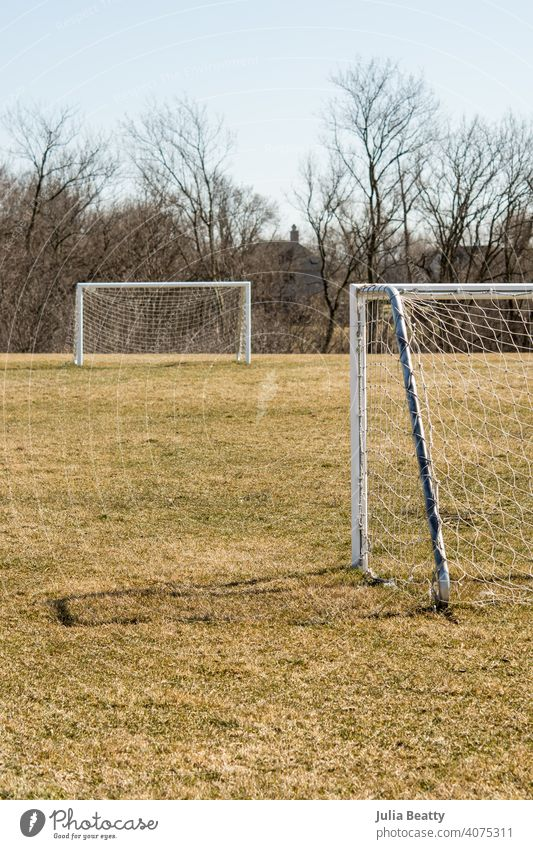 Worn soccer goals in a school field in the spring; bare trees and yellow grass football net sport green game playground gym class physical education p.e.