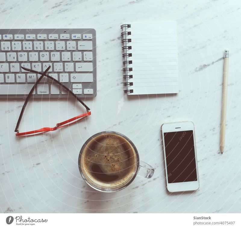 Workplace with notebook, coffee, smartphone, glasses and keyboard. laptop desk view table office computer cup desktop white above work business background paper